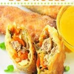 egg rolls on a plate, one cut in half, with a bowl of duck sauce on the side with text overlays that say easy air fryer egg rolls, nowcookthis.com