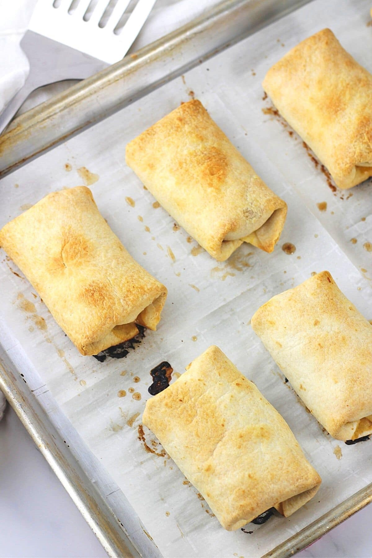 baked chicken chimichangas on a baking sheet with parchment paper