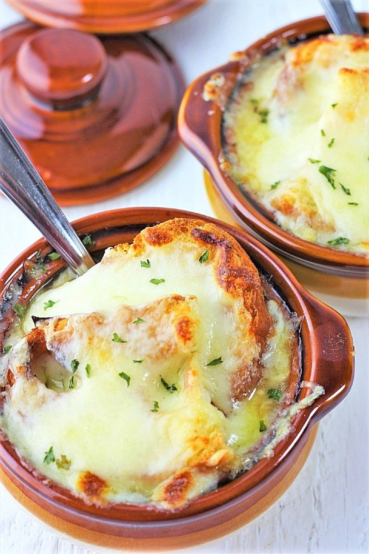 two crocks of easy homemade french onion soup with spoons in them and crock lids in the background