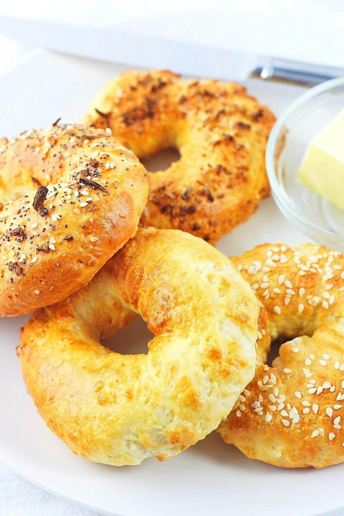 air fryer bagels on a white plate with butter and a knife