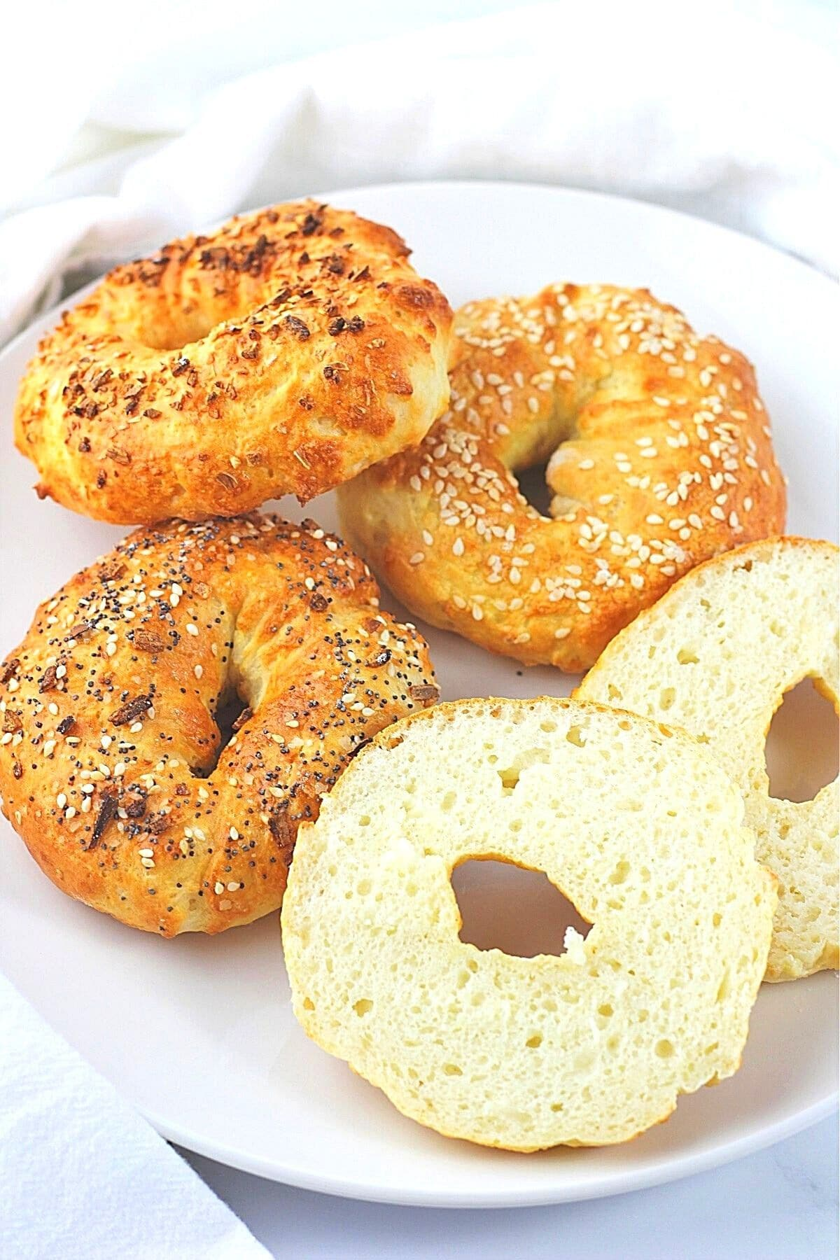 air fryer bagels on a white plate with one bagel cut in half showing the inside
