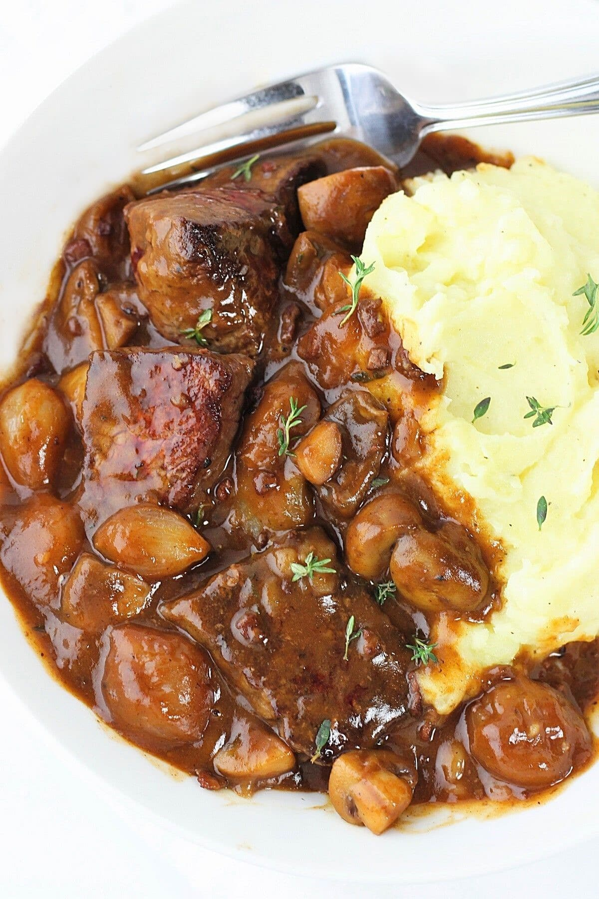 quick and easy beef bourguignon in a bowl with mashed potatoes and a fork