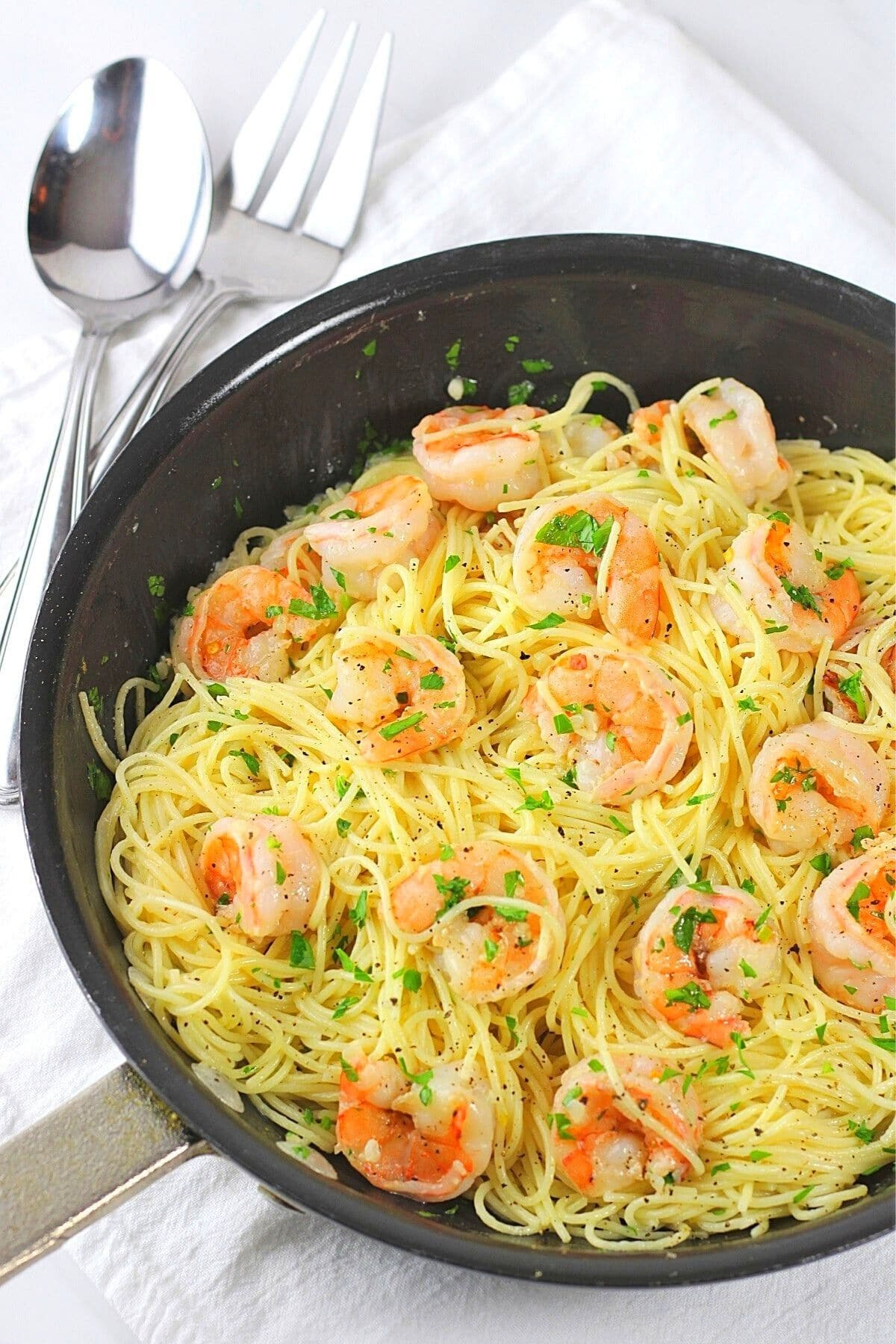 shrimp scampi with angel hair pasta in a pan with a serving spoon and fork on the side