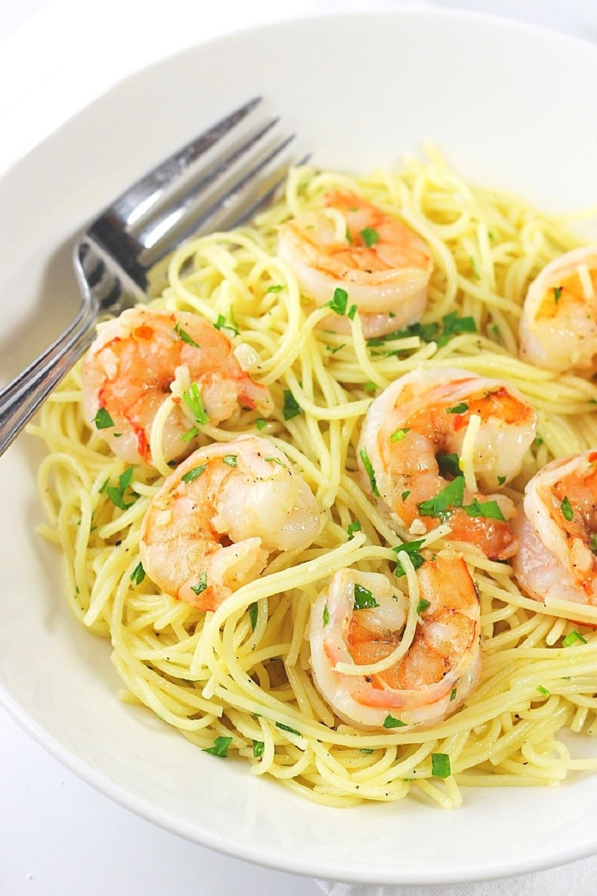 shrimp scampi with angel hair pasta in a white bowl with a fork