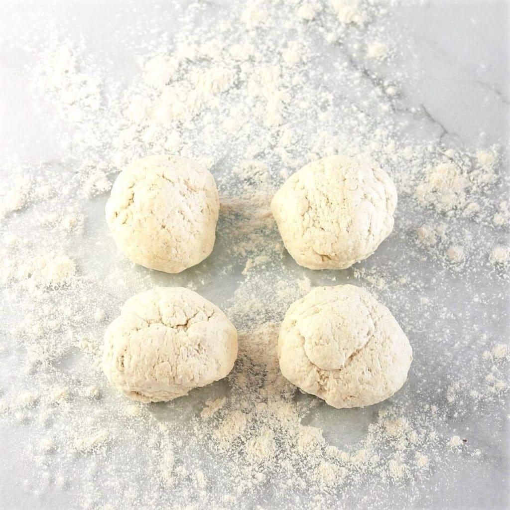 4 dough balls on a floured surface