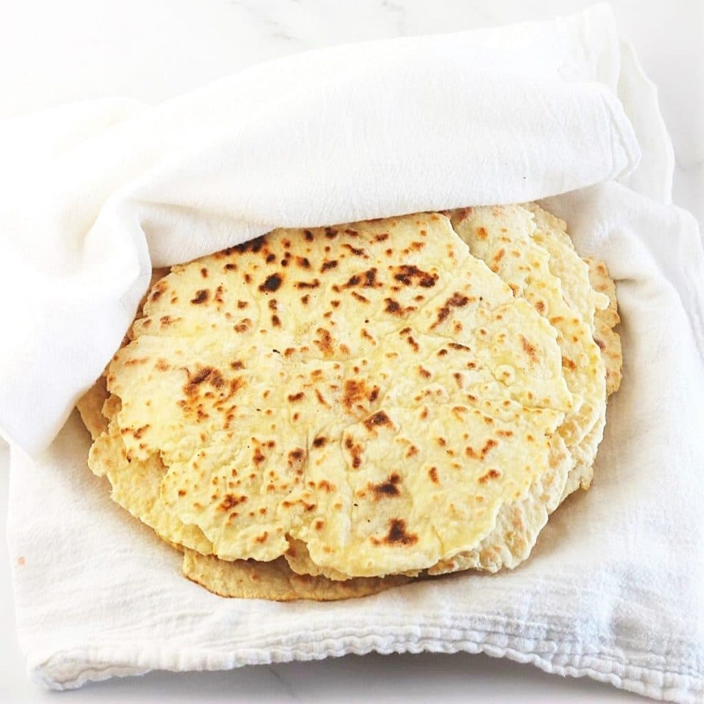 cooked flatbreads partially wrapped in a towel