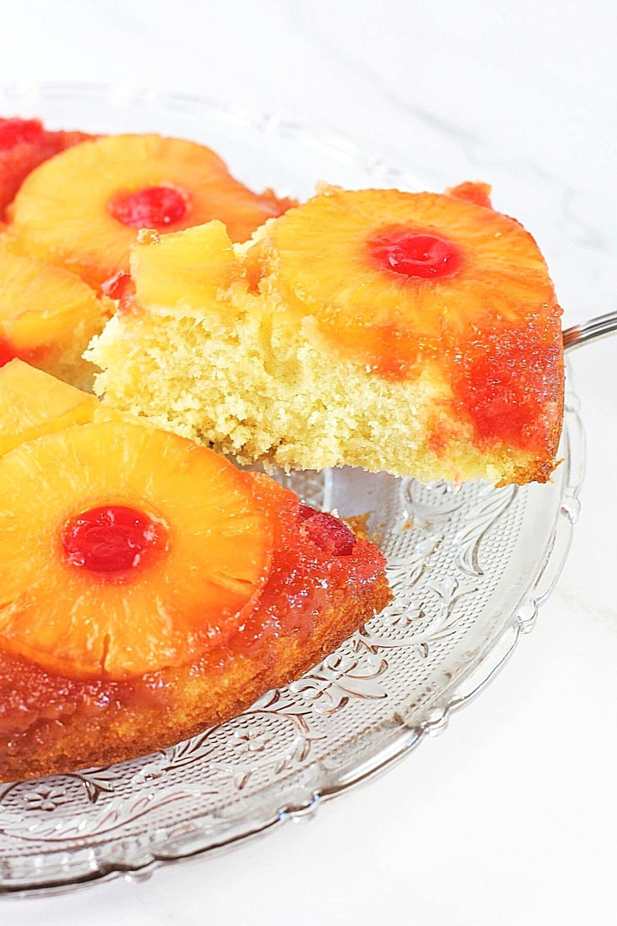 piece of pineapple upside-down cake being lifted from the whole cake with a cake server