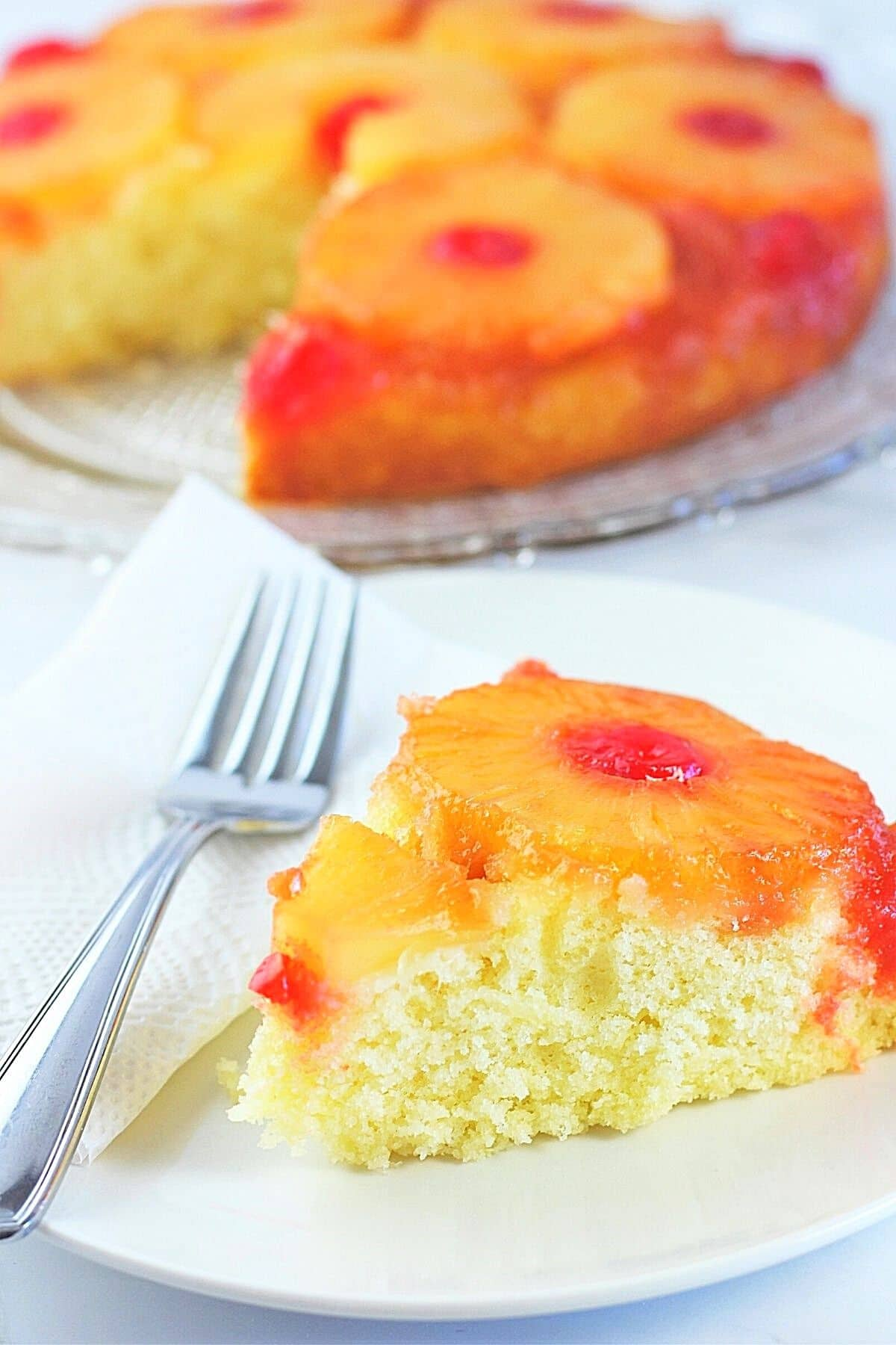 slice of pineapple upside-down cake on a white plate with a napkin and fork with the whole cake in the background