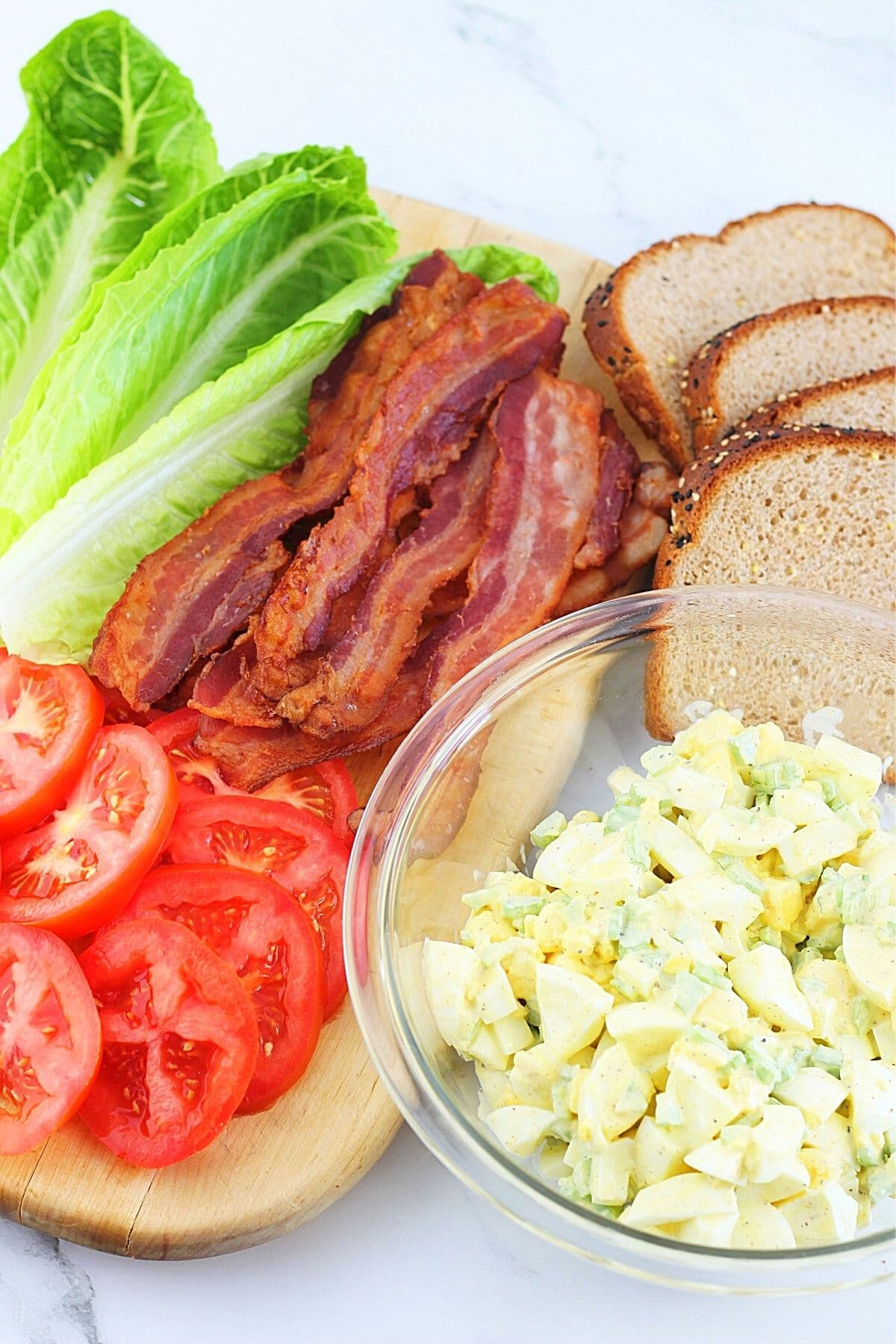 a bowl of egg salad surrounded by sliced tomatoes, cooked bacon, romaine lettuce leaves, and slices of bread
