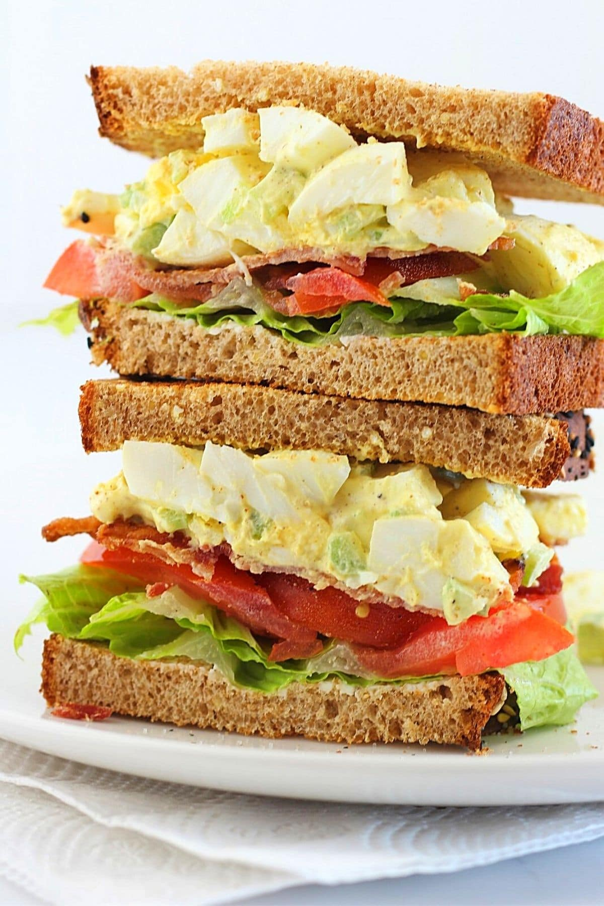 two halves of an egg salad BLT sandwich stacked on top of one another