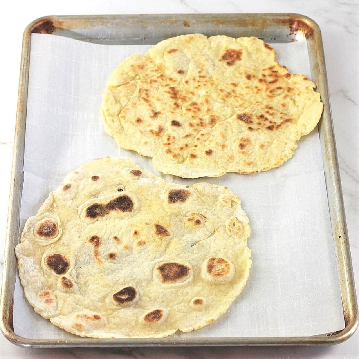 two flatbreads on a baking sheet lined with parchment paper