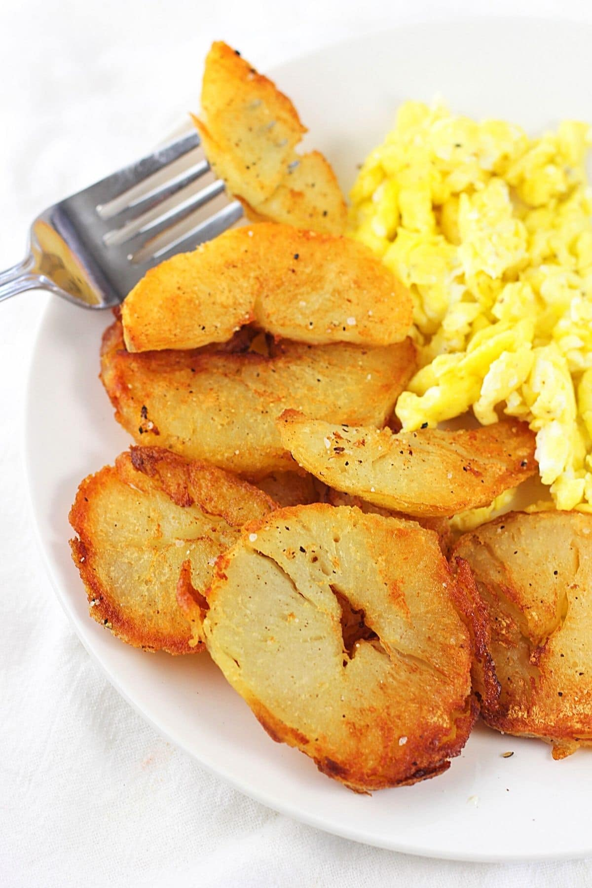 leftover baked potato home fries on a white plate with scrambled eggs with one piece of potato on a fork