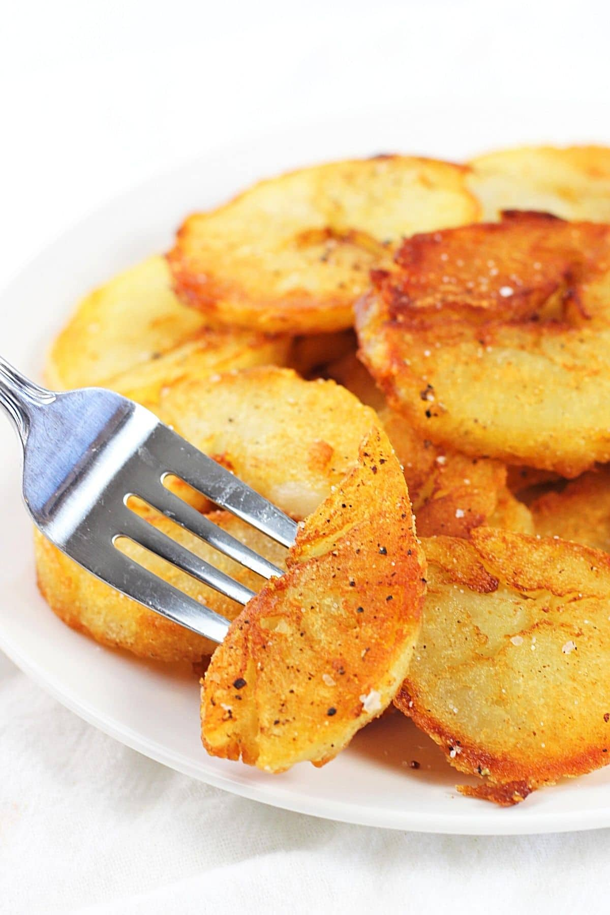leftover baked potato home fries on a white plate with a fork piercing one piece of potato