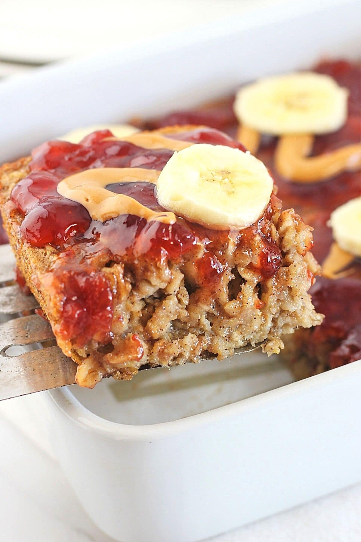 square of peanut butter, banana and jam baked oatmeal being lifted out of the baking dish