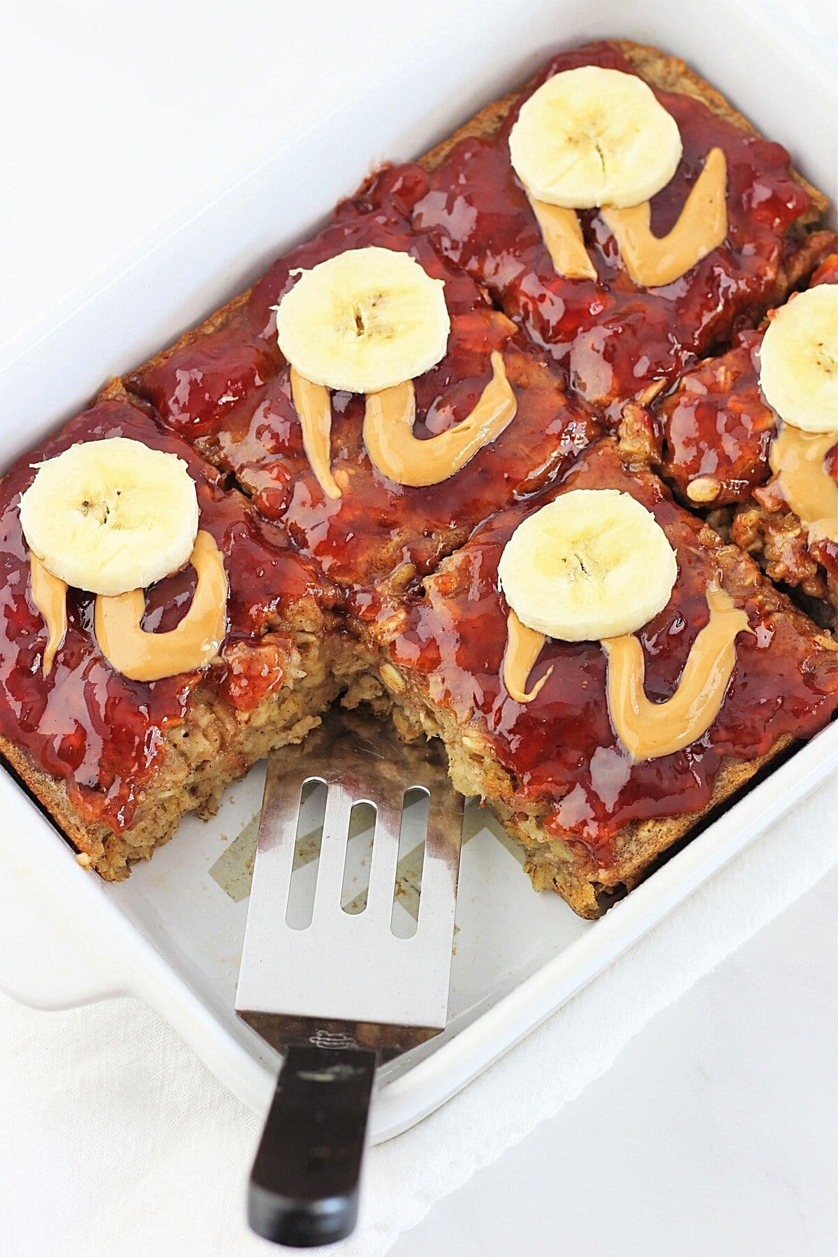 peanut butter, banana and jam baked oatmeal in a baking dish with a spatula