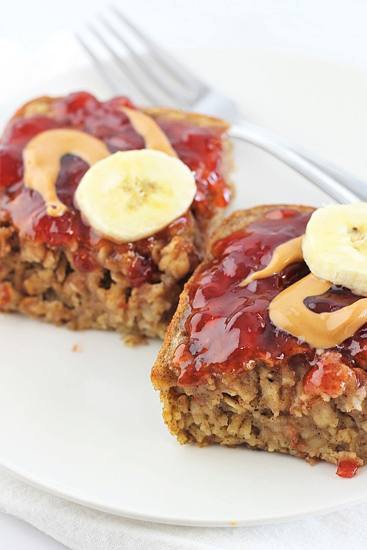 two pieces of peanut butter banana baked oatmeal on a white plate with a fork