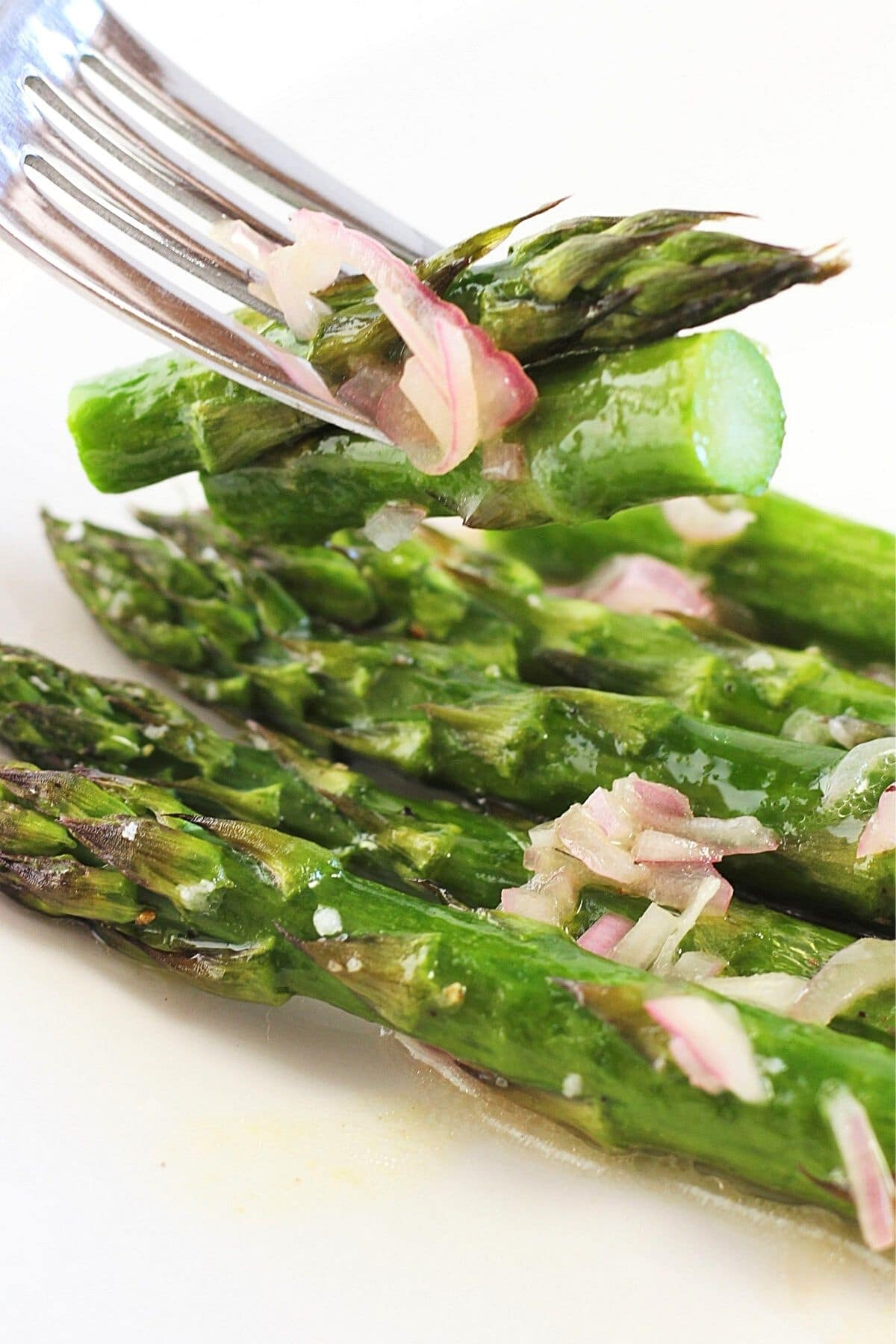 roasted asparagus with shallot vinaigrette on a plate with a forkful of cut asparagus above it