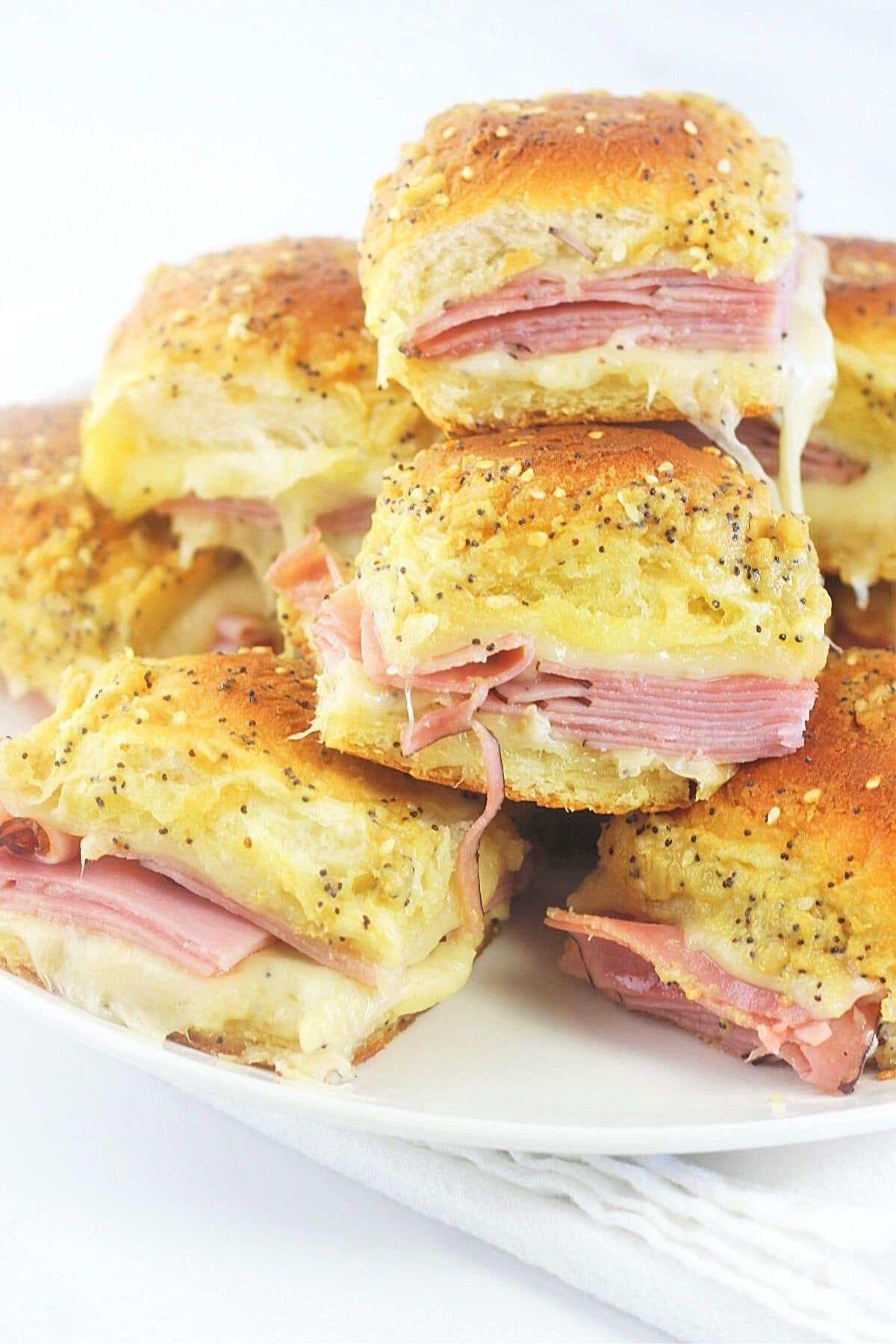 baked ham and cheese sliders with maple, mustard and horseradish piled on a white plate on top of a white napkin