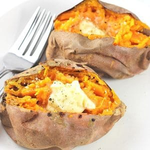 two air-fried baked sweet potatoes topped with butter, salt and pepper on a plate with 2 forks