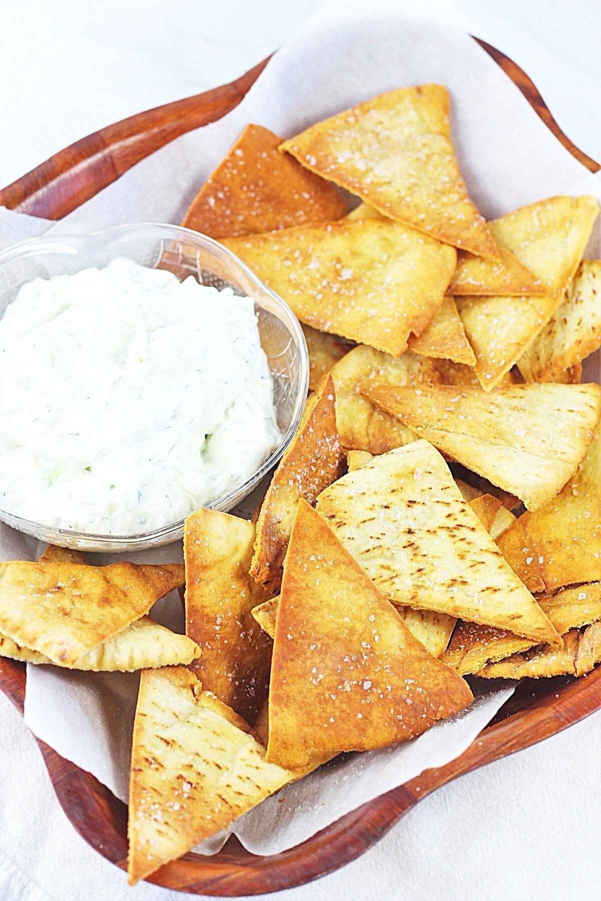 wooden bowl filled with homemade baked pita chips and a bowl of tzatziki