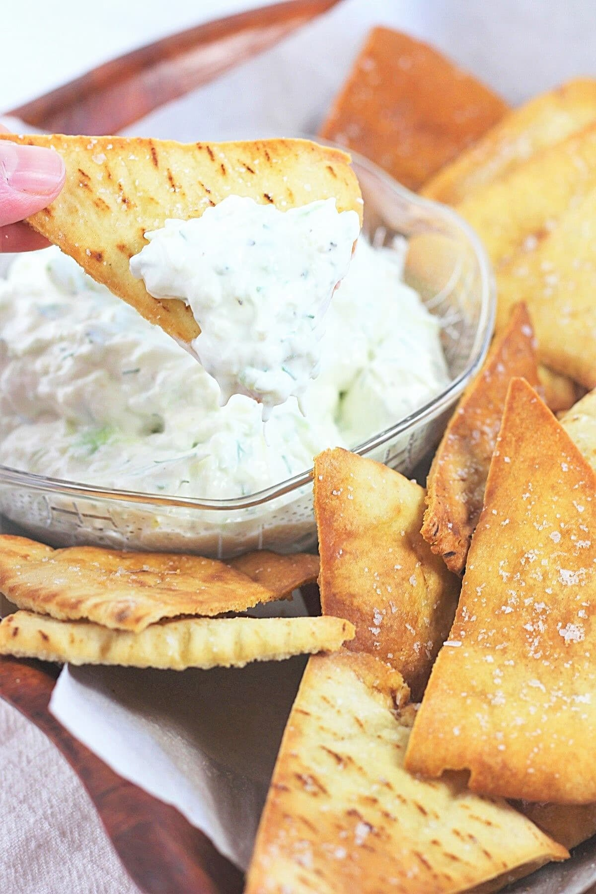 a bowl of homemade baked pita chips with one chip being dipped into a bowl of tzatziki