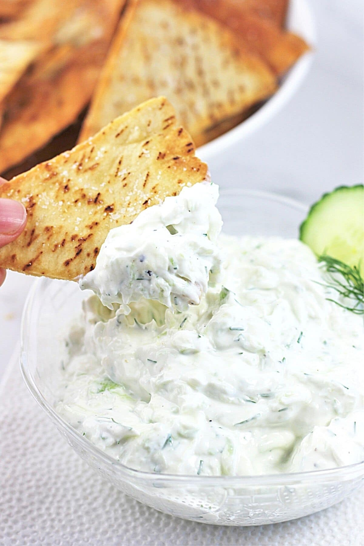 pita chip being dipped into a bowl of homemade tzatziki dip