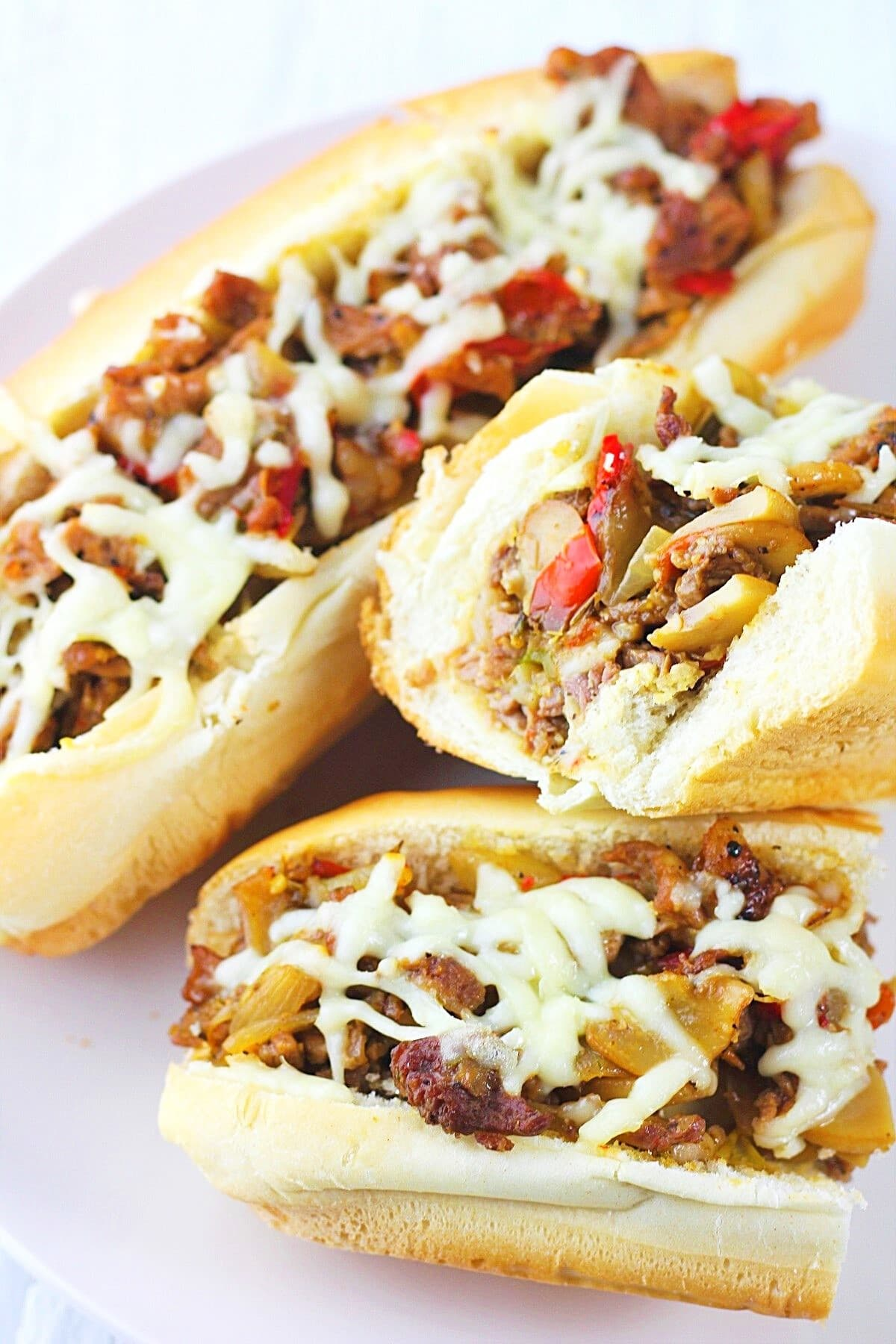 two cheesesteaks with mushrooms, onions and peppers on a white plate, one of them cut in half so you can see the inside