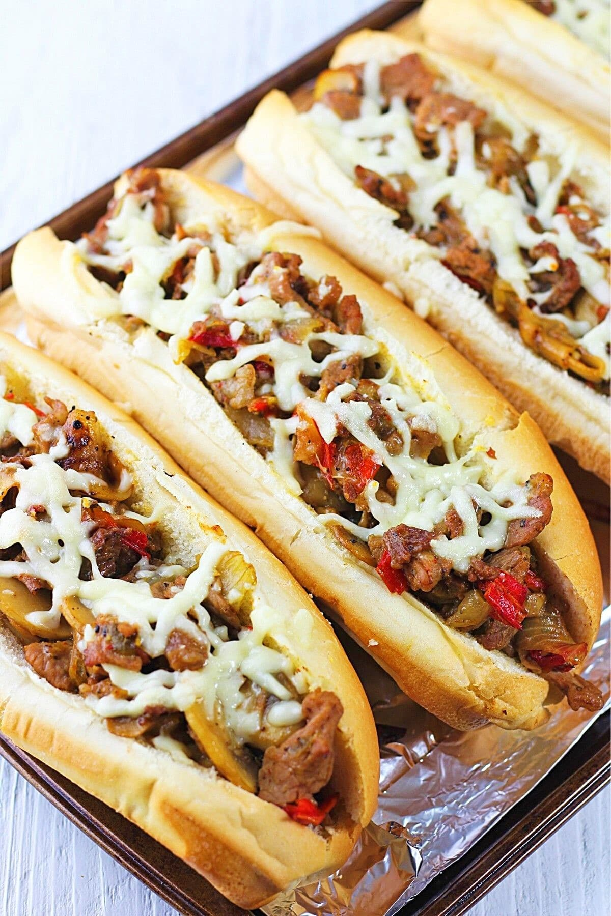 four cheesesteaks with mushrooms, onions and peppers on a baking sheet