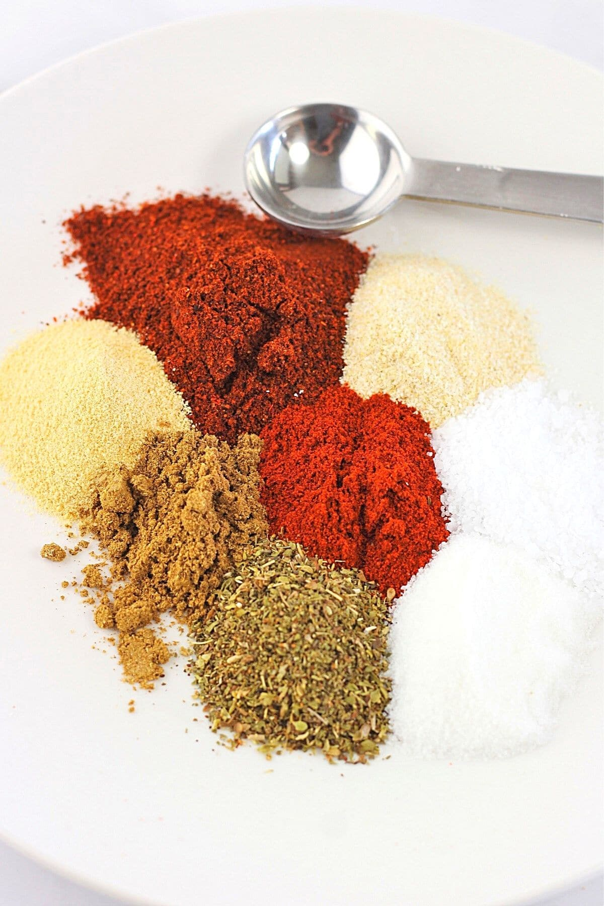 herbs and spices on a plate with a measuring spoon