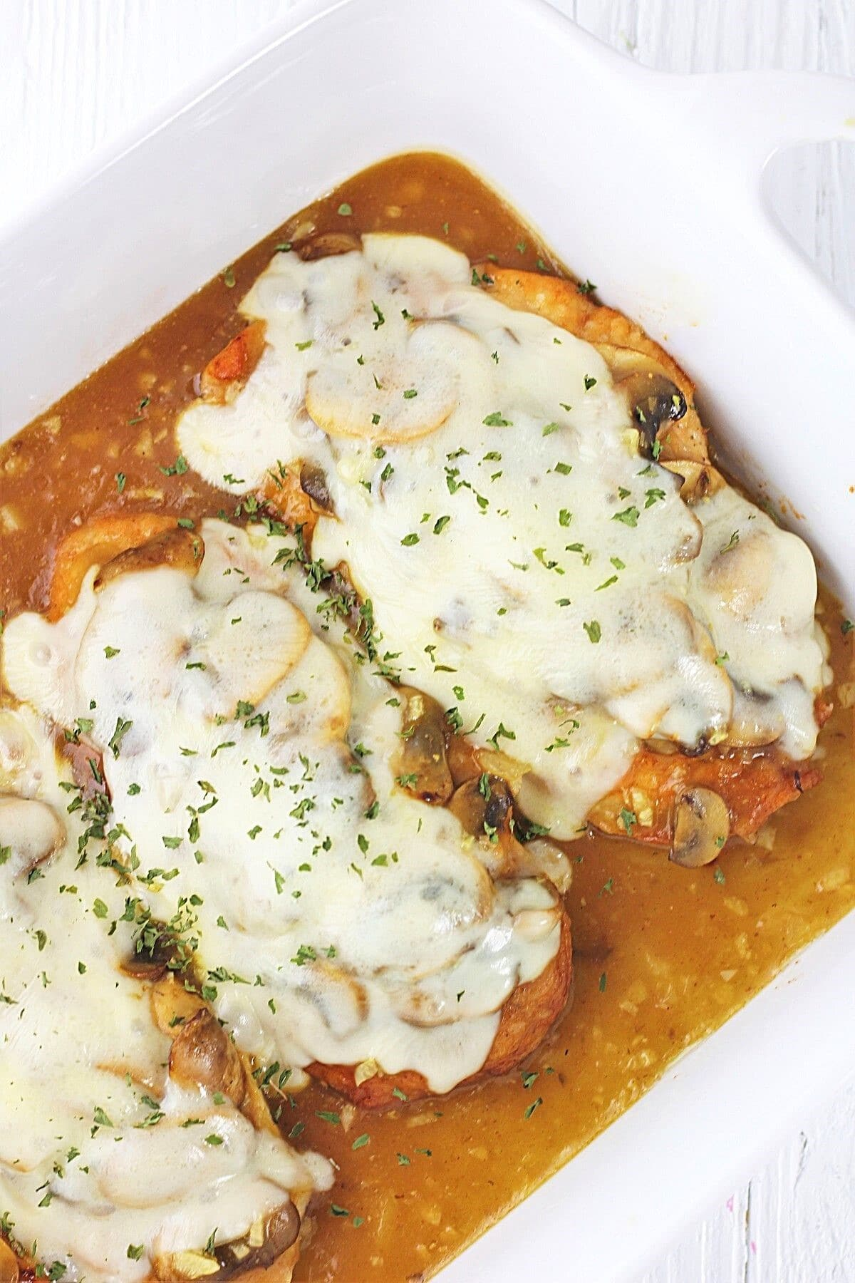 cheesy chicken and mushrooms in a  white baking dish sprinkled with parsley