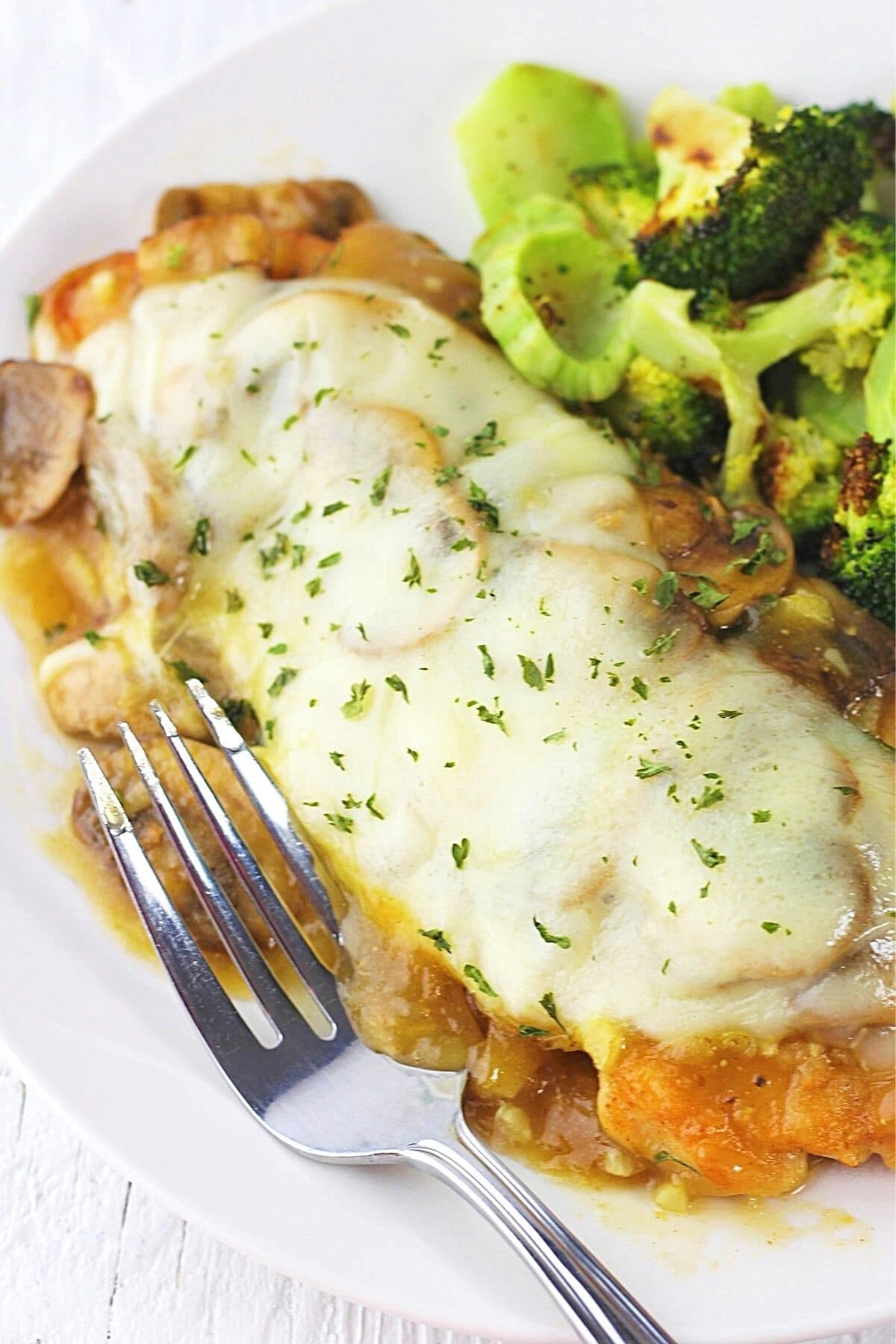 piece of cheesy chicken with mushrooms on a plate with roasted broccoli and a fork