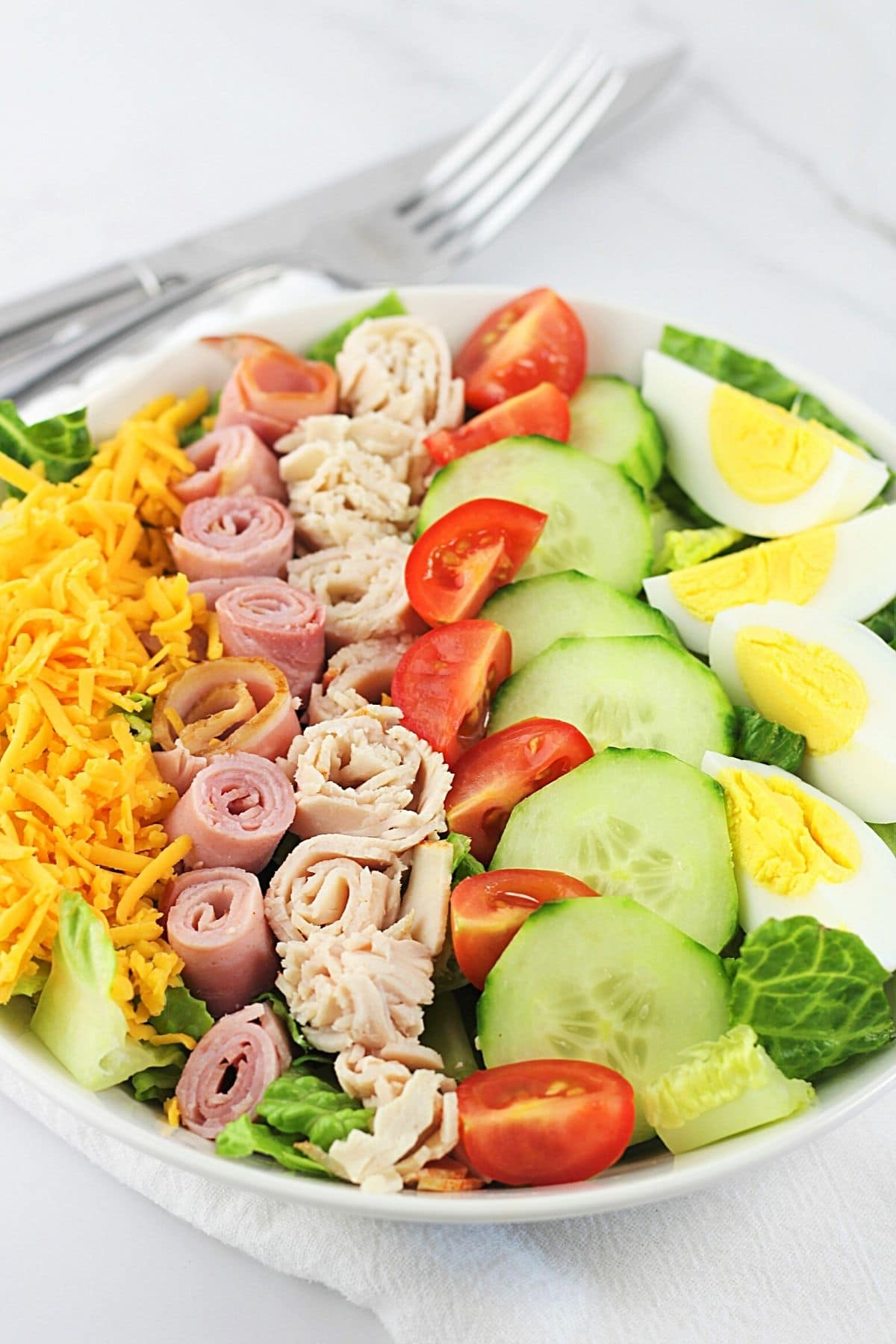 arranged classic chef salad in a white bowl with a knife and fork on the side