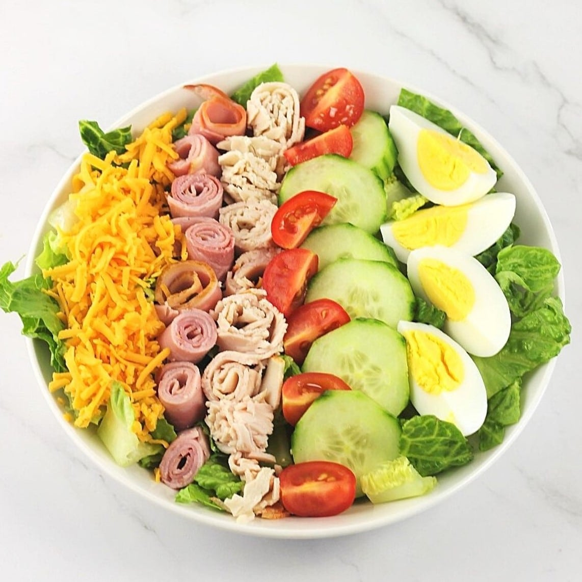 bowl of lettuce topped with shredded cheese, rolled and sliced deli ham and turkey, quartered cherry tomatoes, sliced cucumber, and hard-boiled egg quarters