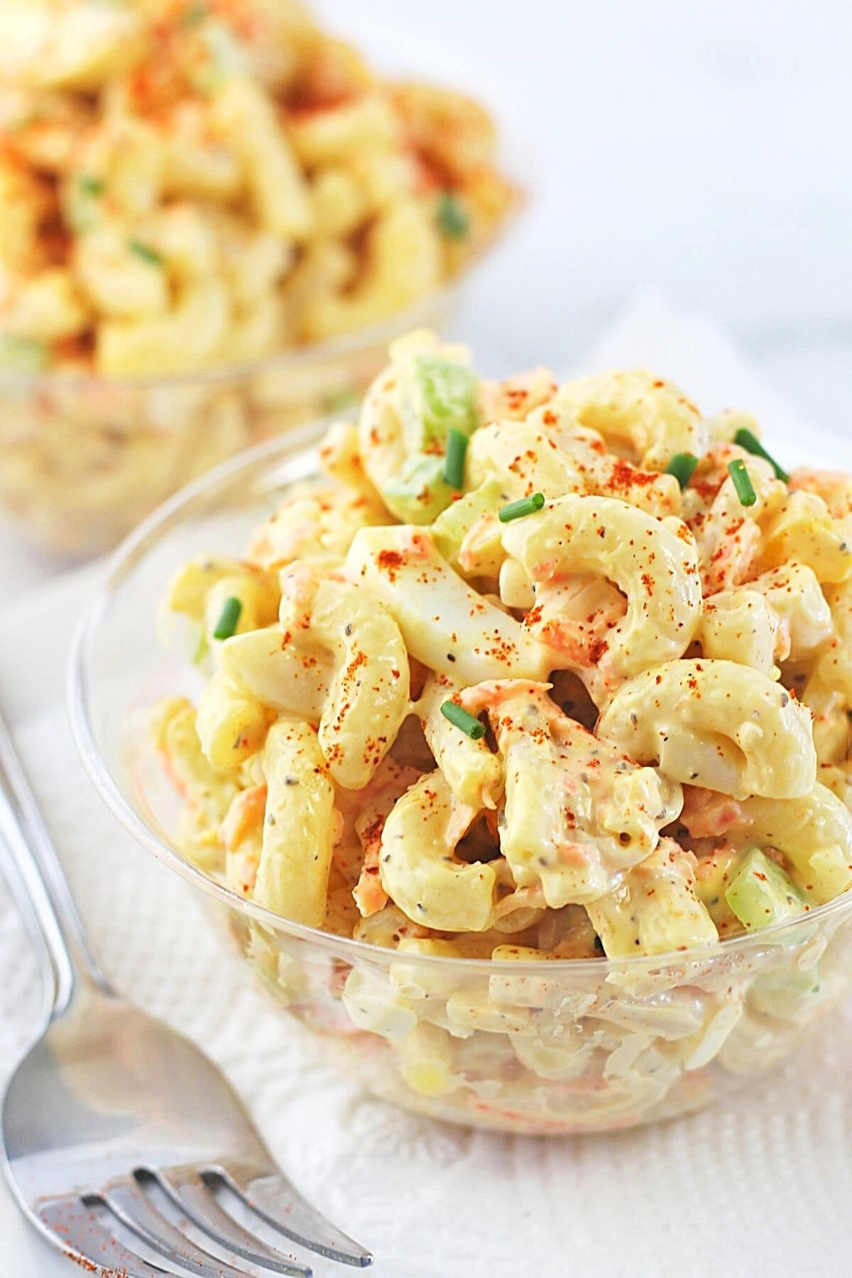 two small bowls of classic creamy macaroni salad with a fork on the side