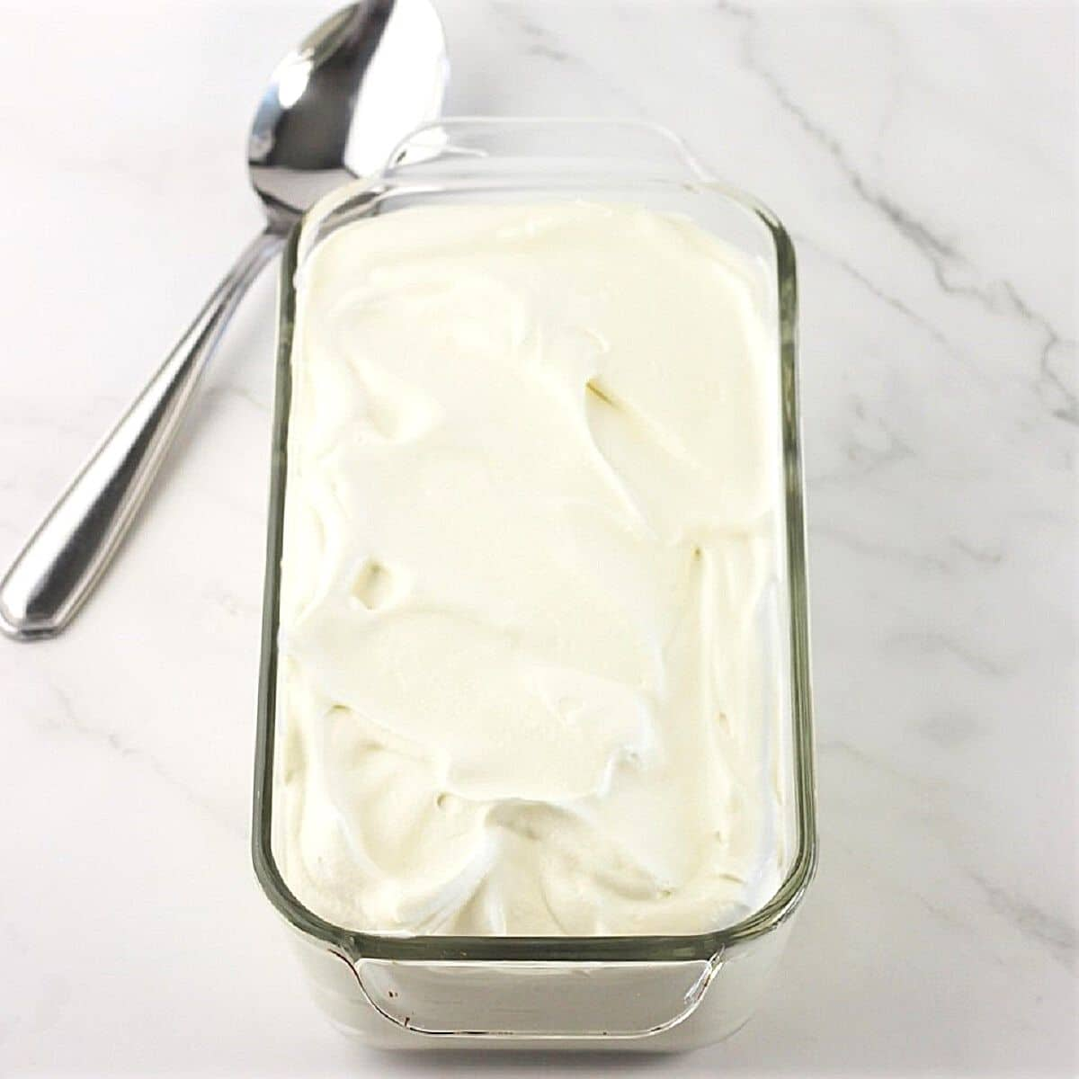 whipped cream mixture in a glass loaf pan with a spoon on the side