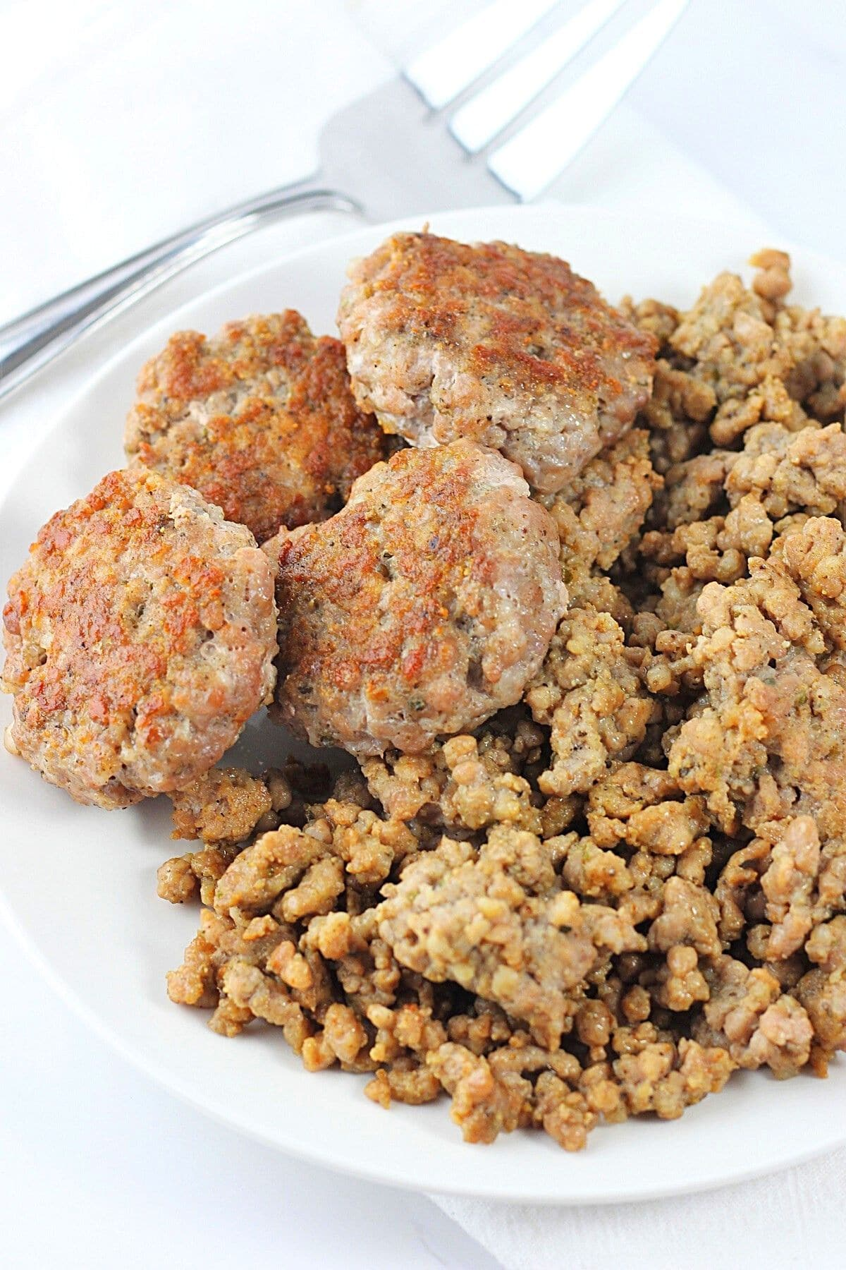 homemade breakfast sausage patties and crumbles on a white plate