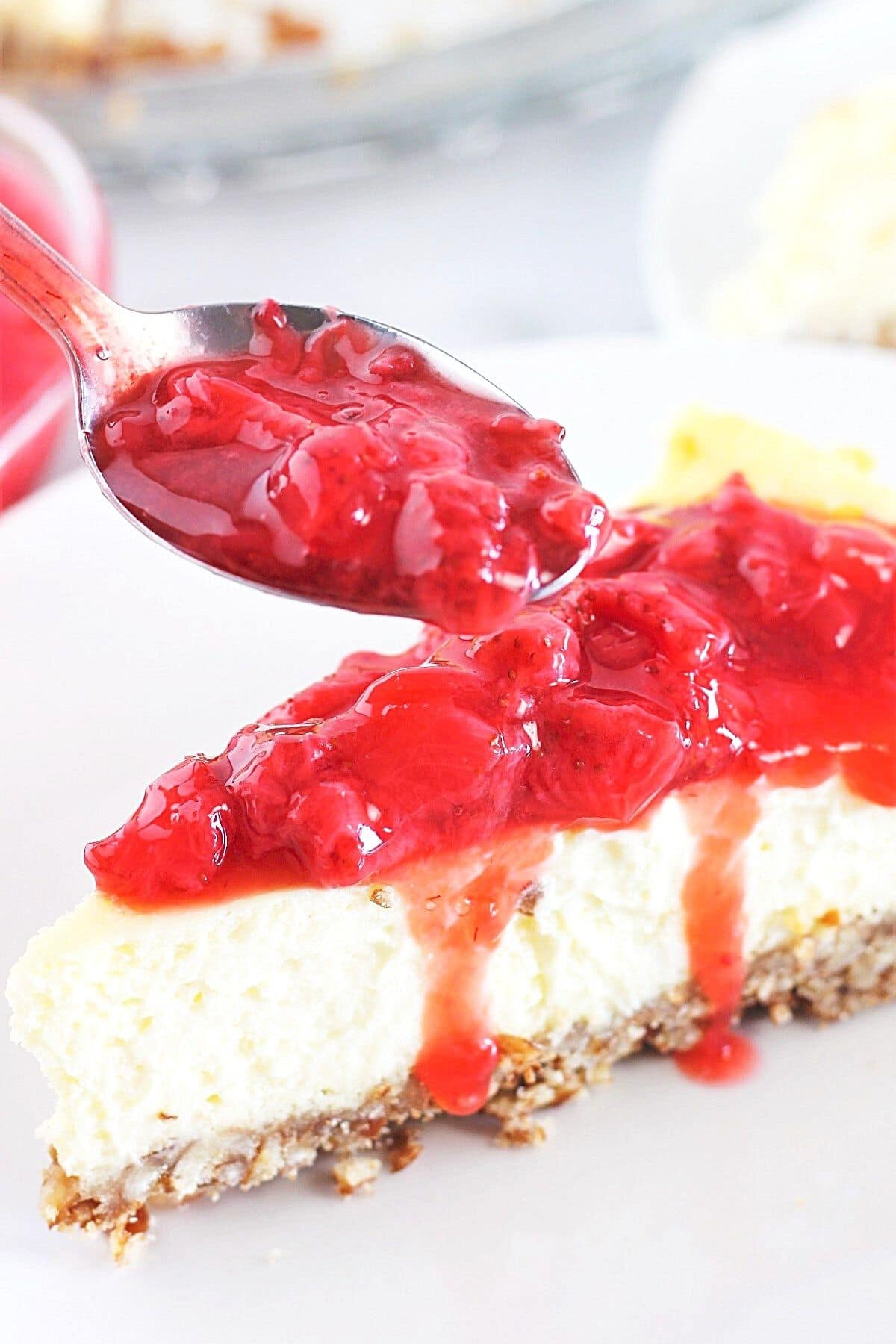 piece of cheesecake on a white plate with a spoonful of homemade fresh strawberry sauce being put on top