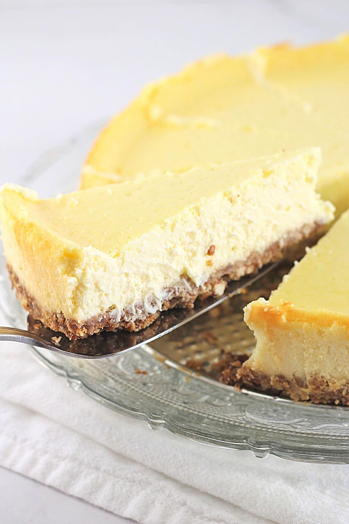 a slice of plain vanilla cheesecake with pretzel crust being lifted away from the whole cheesecake