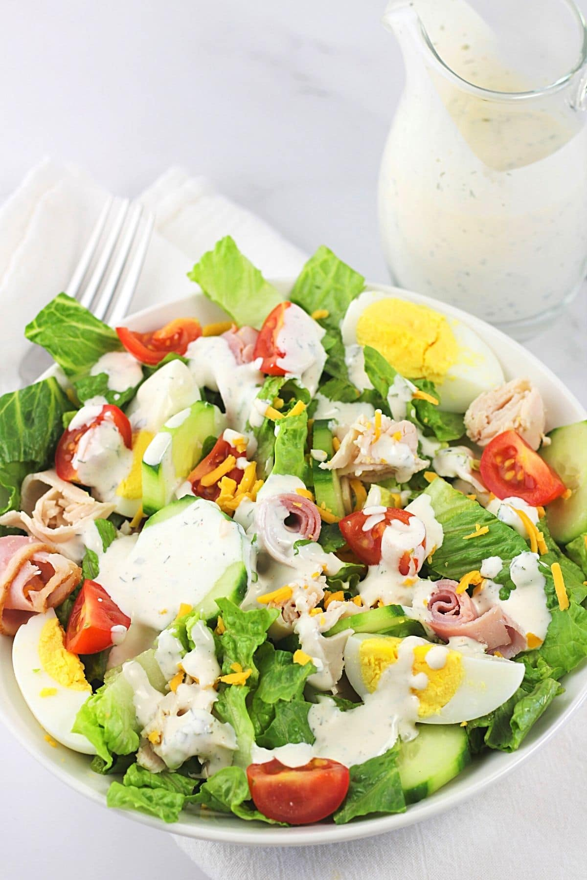 salad drizzled with easy homemade ranch dressing with a small pitcher of the dressing and a fork on the side