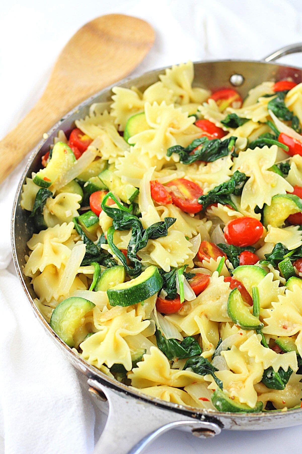 farfalle pasta with zucchini, spinach and tomatoes in a pan with a wooden spoon on the side