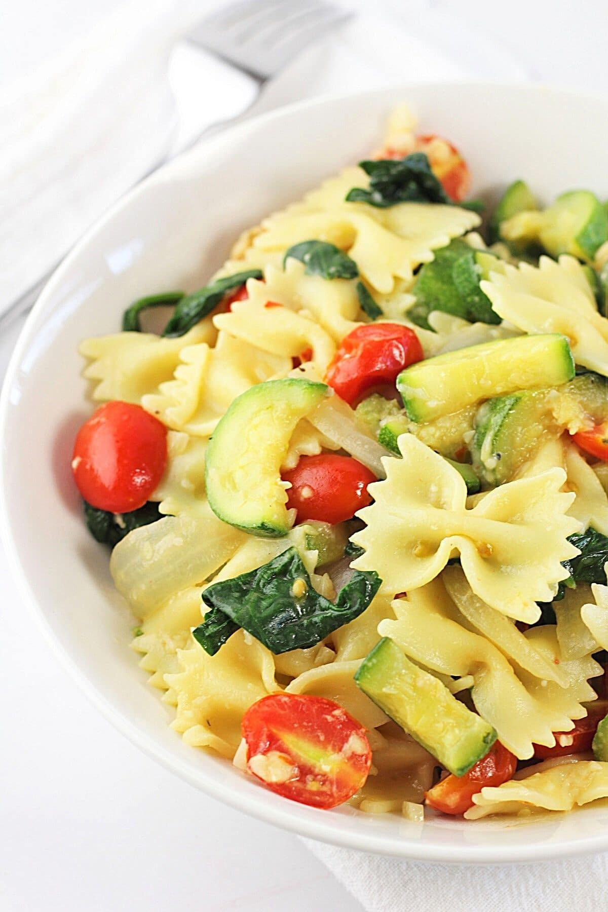 farfalle pasta with zucchini, spinach and tomatoes in a white bowl with a fork on the side
