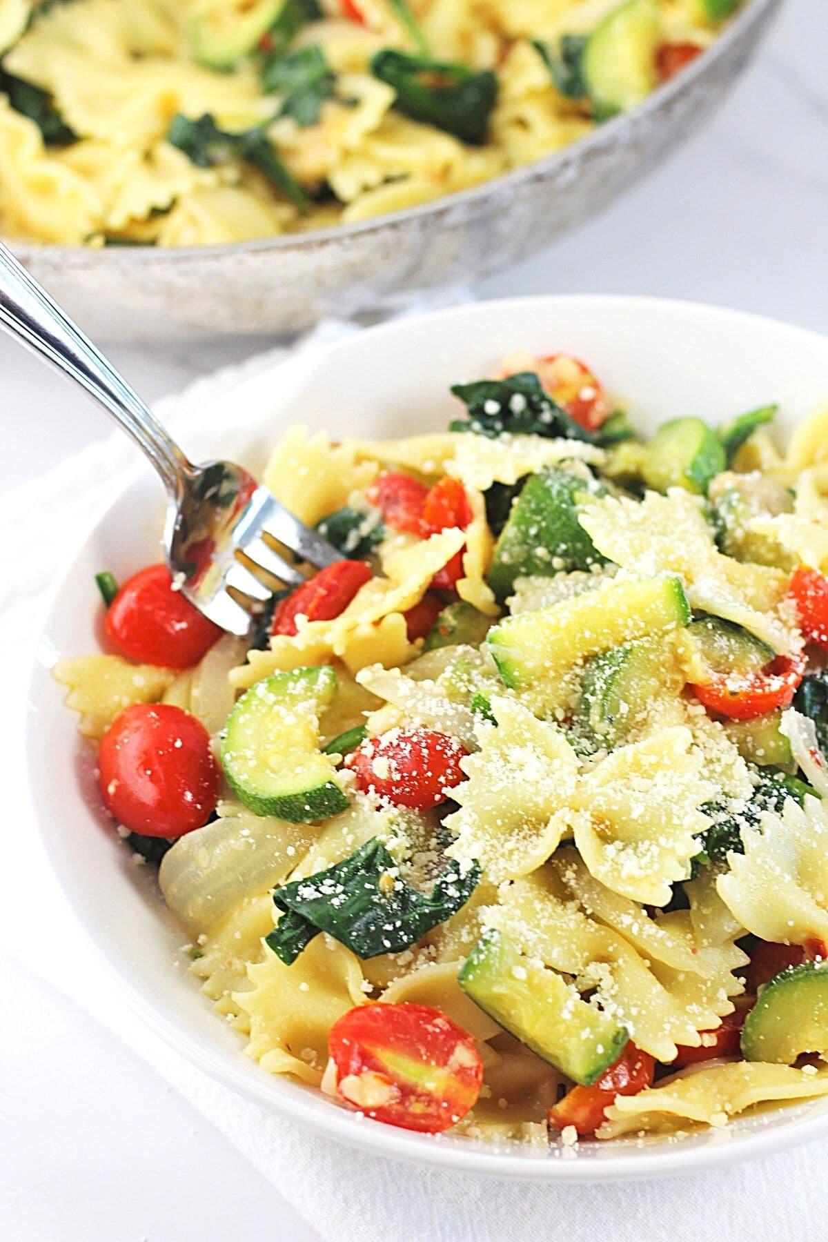 bowl of farfalle pasta with zucchini, spinach and tomatoes sprinkles with grated parmesan cheese and a forkful being taken out