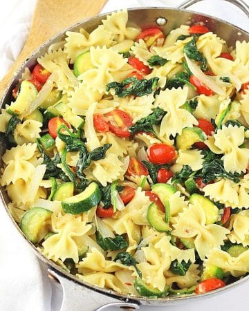farfalle with zucchini, spinach and tomatoes in a pan with a wooden spoon on the side