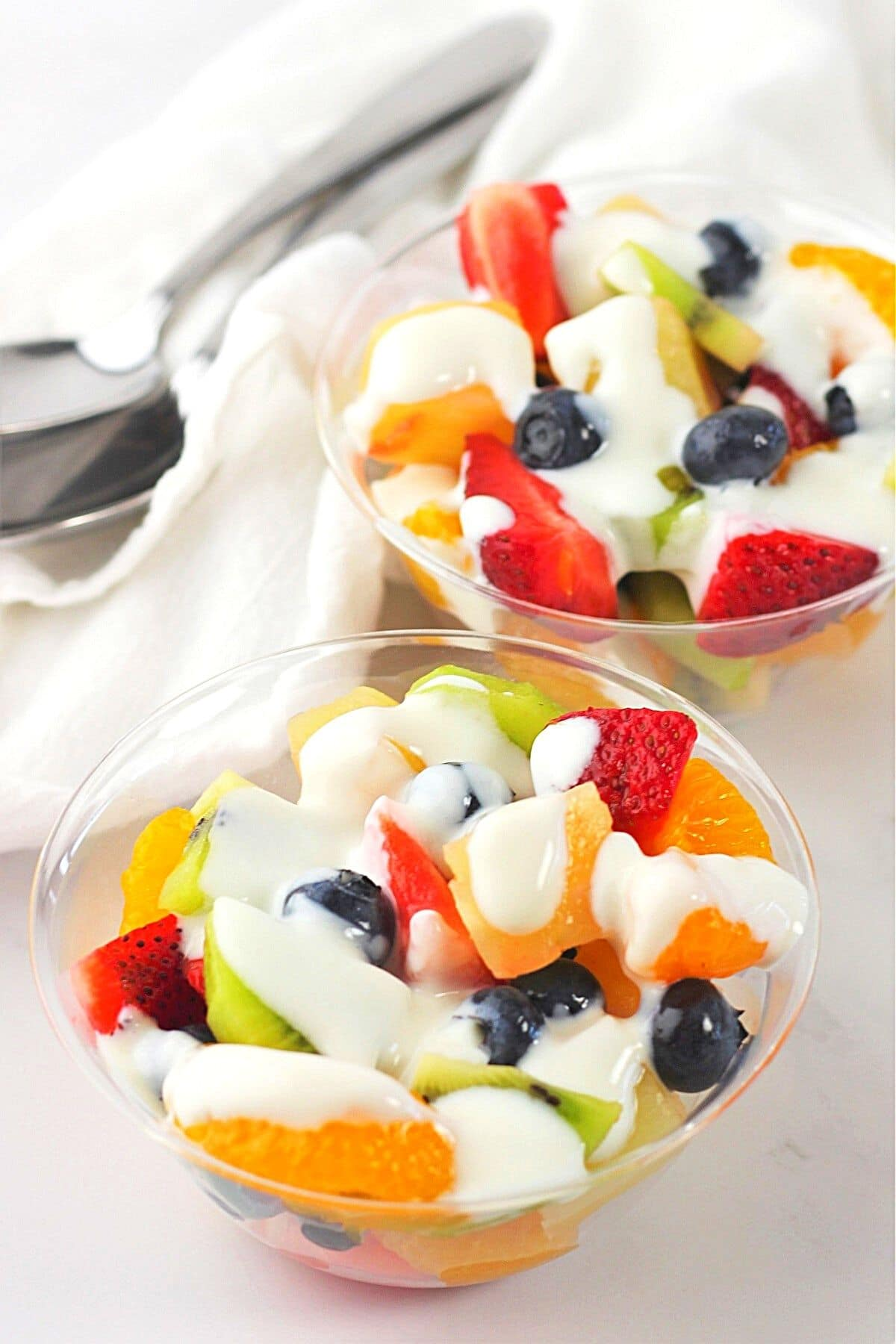 two individual serving bowls of fruit salad, each drizzled with creamy vanilla yogurt dressing, with a napkin and two spoons on the side