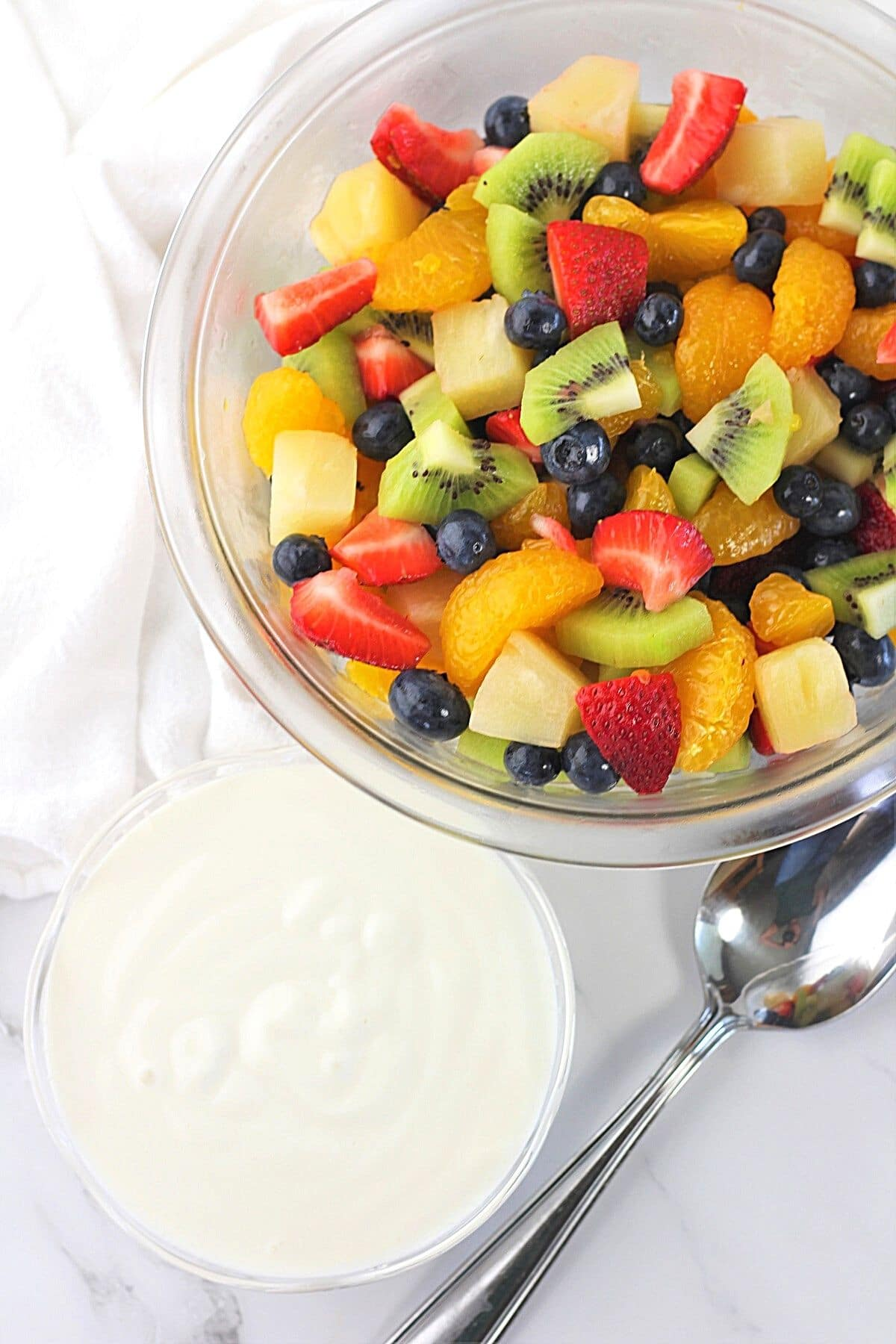 a large bowl of fruit salad with a smaller bowl of creamy vanilla yogurt dressing and a spoon on the side