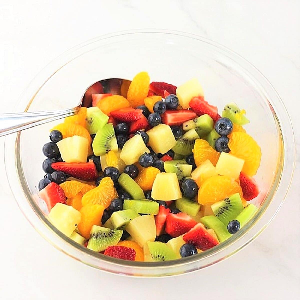 chopped strawberries, blueberries, sliced kiwi, pineapple chunks, and mandarin oranges tossed together in a bowl with a spoon