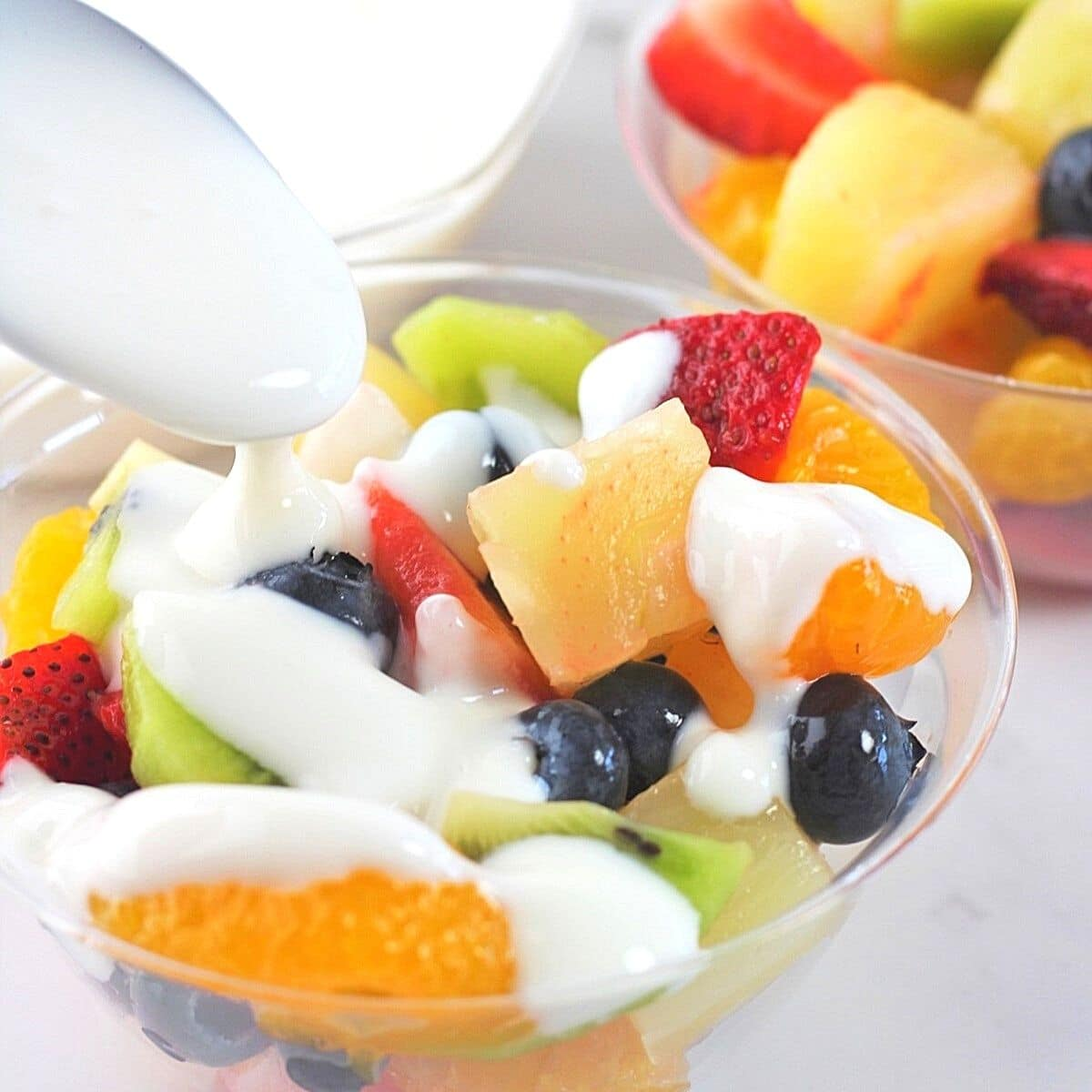 two individual serving bowls of fruit salad, one being drizzled with vanilla yogurt dressing