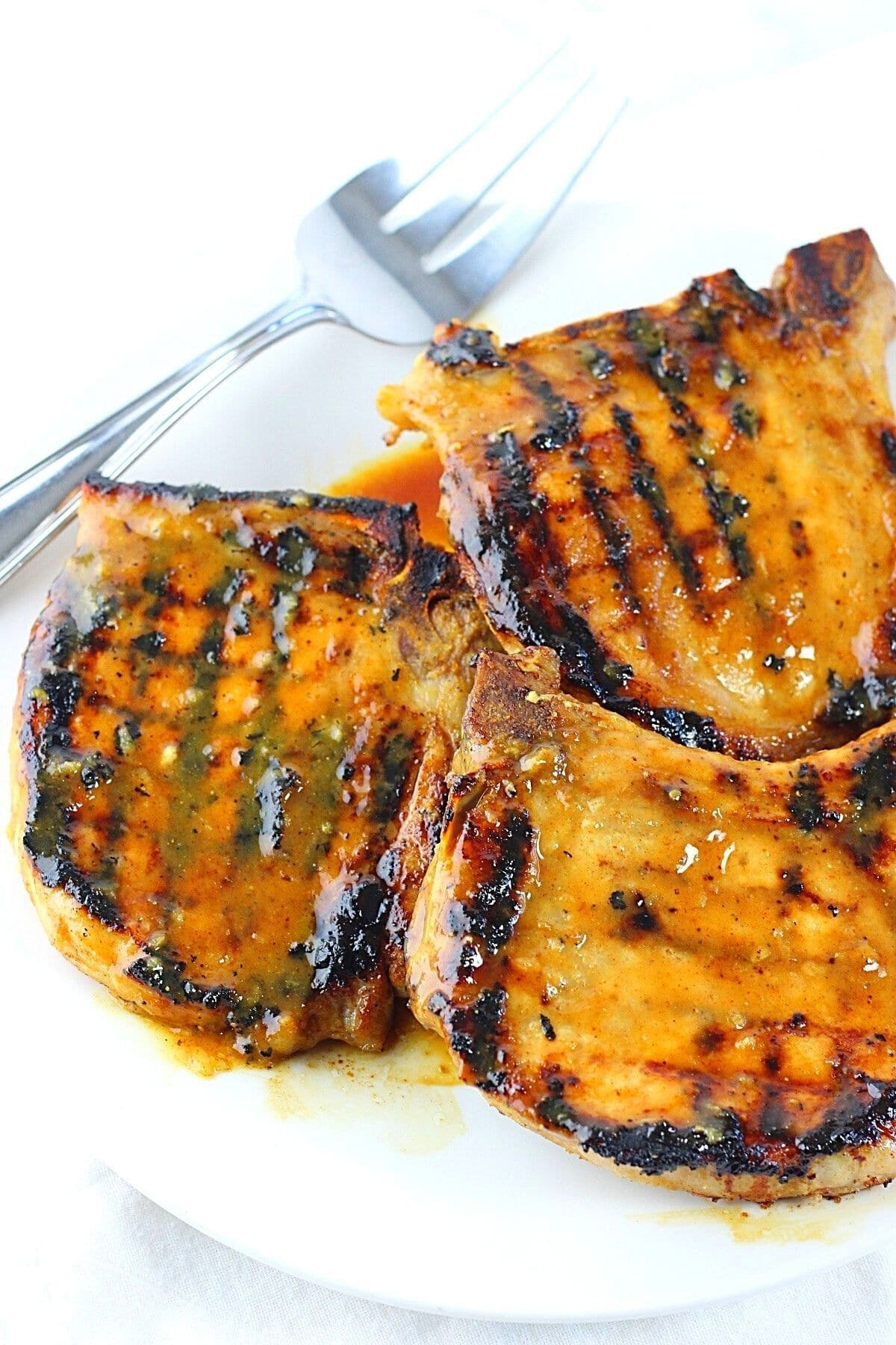 honey mustard grilled pork chops on a white plate with a serving fork on the side