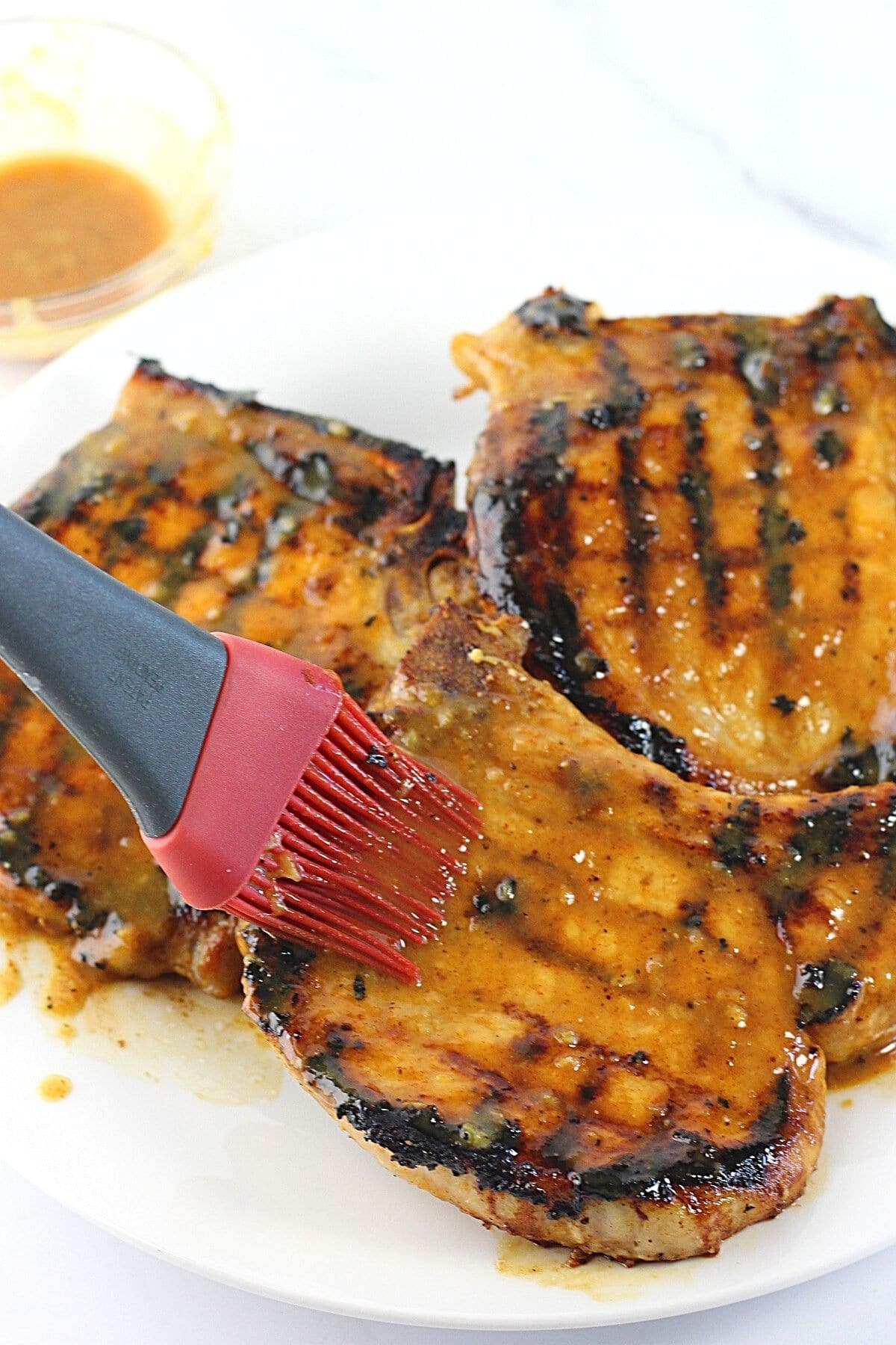 grilled pork chops being brushed with honey mustard marinade