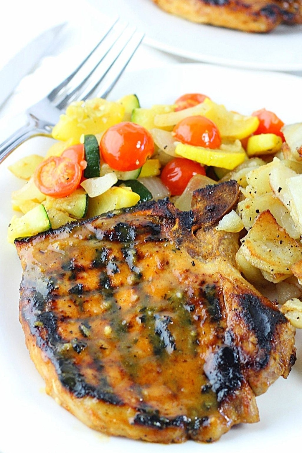 honey mustard grilled pork chop on a plate with vegetables and potatoes and a fork on the side